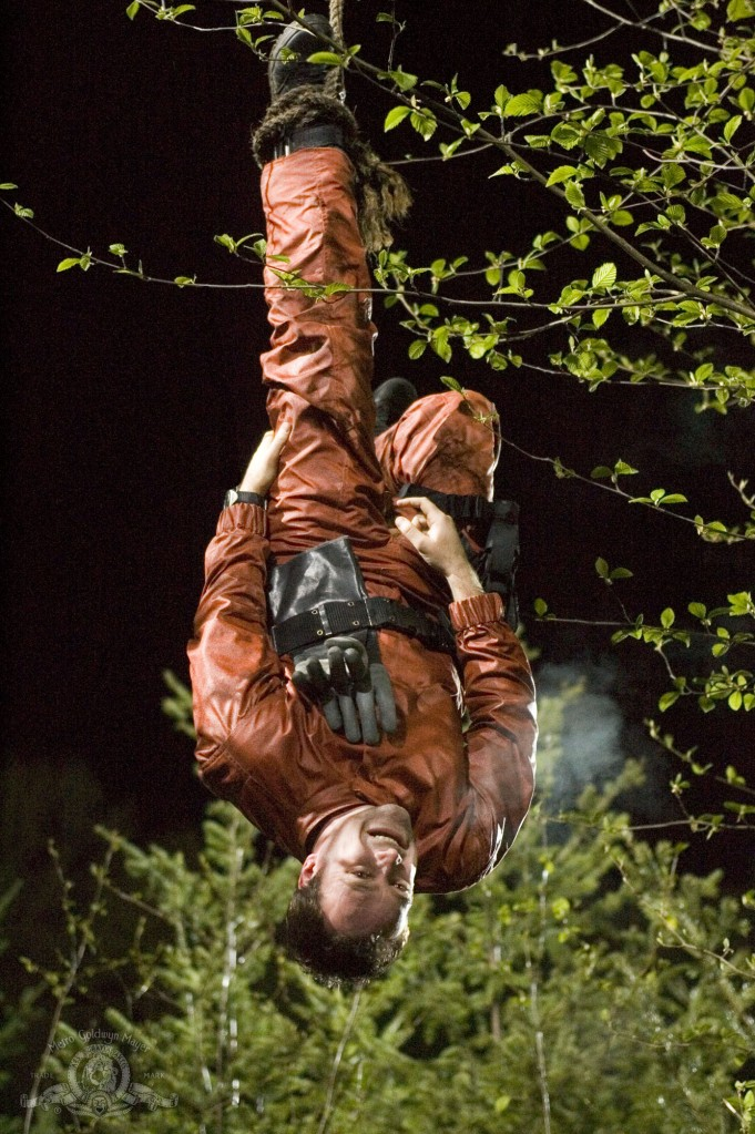 Rodney McKay hung upside down in a tree in 'Runner'
